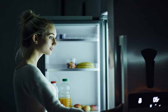 Woman looking inside fridge